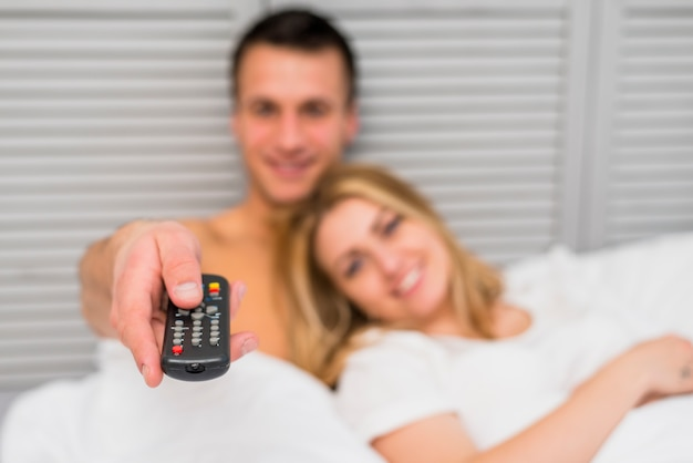 Young couple watching tv in bed
