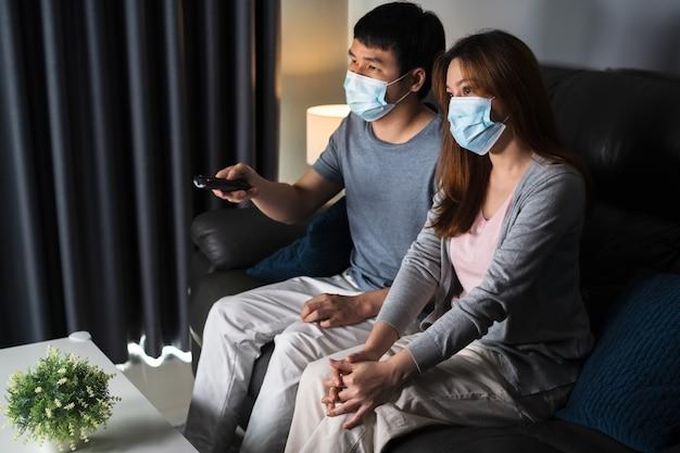 Молодая пара смотрит телевизор на диване и носит медицинскую маску для защиты от коронавируса (covid-19)