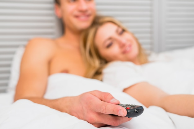 Young couple watching tv in white bed