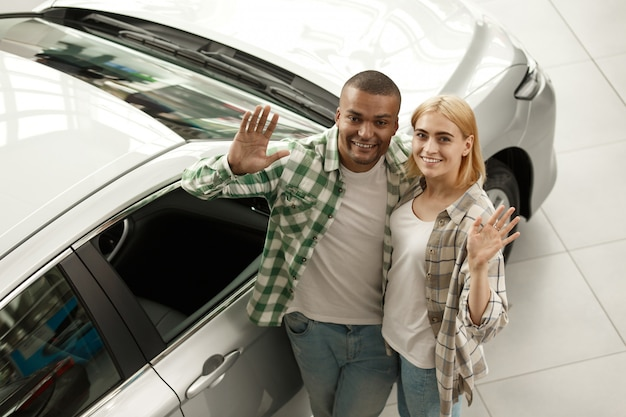 Young couple waving to the camera at the dealership salon, copy space.