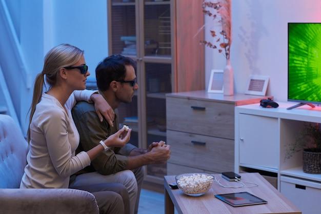 ポップコーンを食べて、自宅の暗い部屋で映画を見ているソファに座って3dメガネをかけている若いカップル