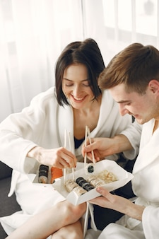 寿司を食べるバスローブを着ている若いカップル。 Premium写真