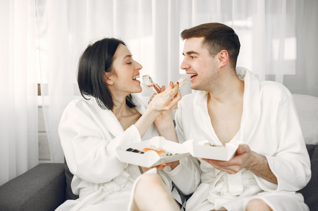 Young couple wearing bathrobes eating sushi.