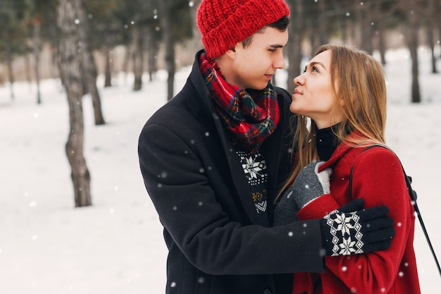 Young couple wearing blanket on a snowy field