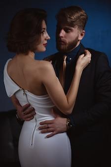 Молодая пара в элегантной одежде и позирует