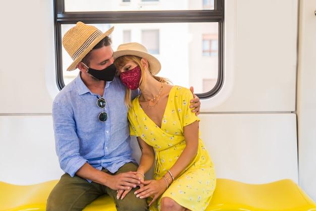 電車の中で座っているフェイスマスクを身に着けている若いカップル