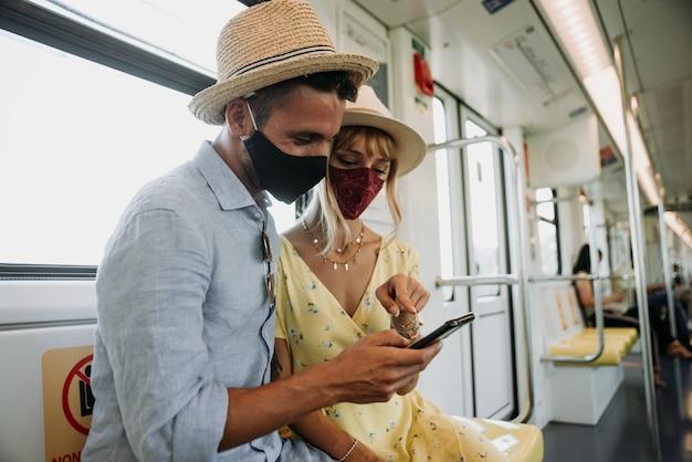 携帯電話のコンタクトトレーシングアプリを使用してフェイスマスクを着用している若いカップル。