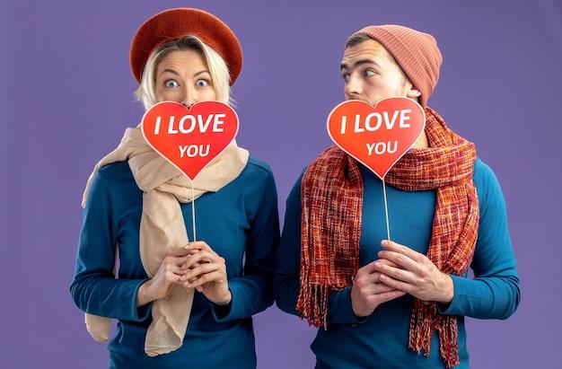 Молодая пара в шляпе с шарфом в день святого валентина закрыла лицо красными сердцами на палочке с текстом я люблю тебя довольным парнем, смотрящим на девушку, изолированную на синем фоне