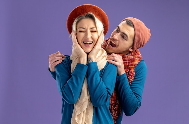 Young couple wearing hat with scarf on valentine's day pleased with closed eyes girl putting hands on cheeks guy standing behind girl isolated on blue background