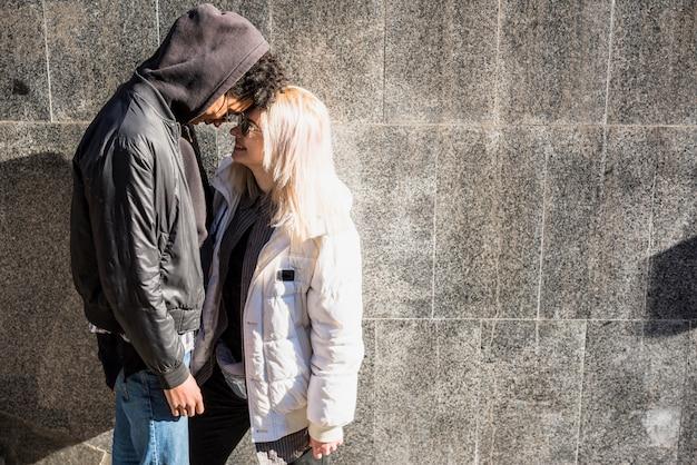 若いカップルが彼の額に触れる灰色の壁に対してジャケットの地位を着て