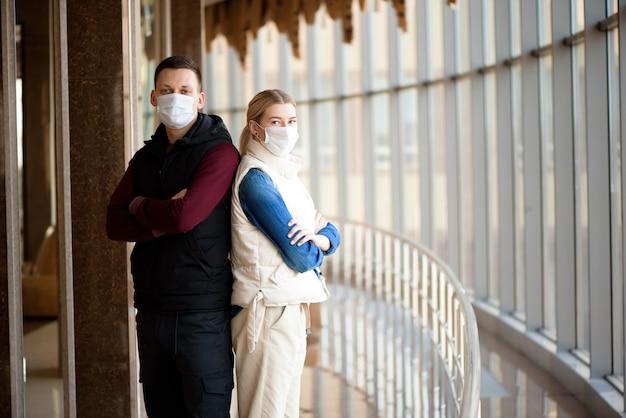 空港ラウンジで医療用マスクを着用した若いカップル