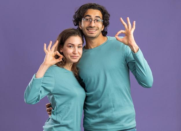 Молодая пара в пижаме, улыбающийся мужчина в очках, держащий довольную женщину за талию, глядя вперед, делает хорошо, знак изолирован на фиолетовой стене
