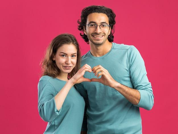 안경을 쓰고 웃는 남자 잠옷을 입은 젊은 부부는 분홍색 벽에 고립되어 함께 하트 사인을 하는 앞을 바라보는 여성을 기쁘게 생각합니다