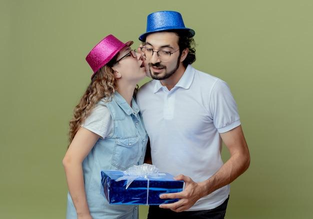 Молодая пара в розово-синей шляпе, девушка шепчет на ухо парню и парень, держащий подарочную коробку, изолированную на оливково-зеленом