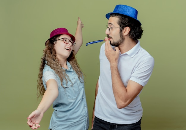 Молодая пара в розовых и голубых шляпах смотрит друг на друга, девушка разворачивает руки, а парень дует в свисток, изолированные на оливково-зеленом