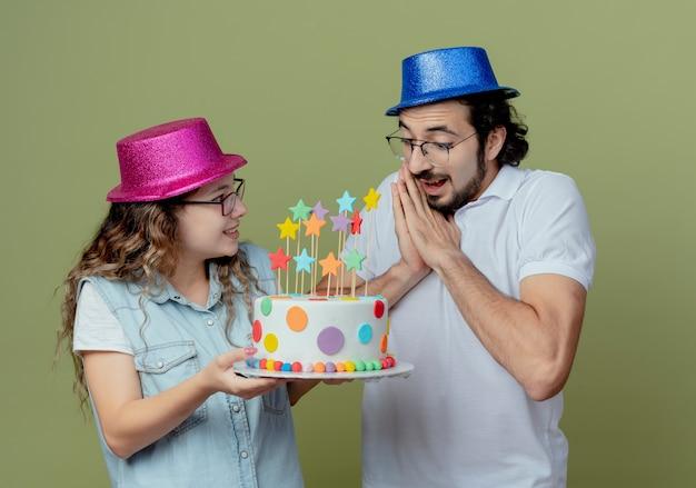 ピンクと青の帽子をかぶった若いカップルが喜んでいる女の子は、オリーブグリーンの壁に隔離された驚いた男にバースデーケーキを与える