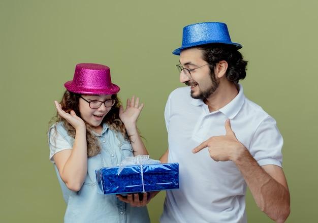 Молодая пара в розово-голубой шляпе улыбающийся парень дарит подарочную коробку удивленной девушке, изолированной на оливково-зеленом