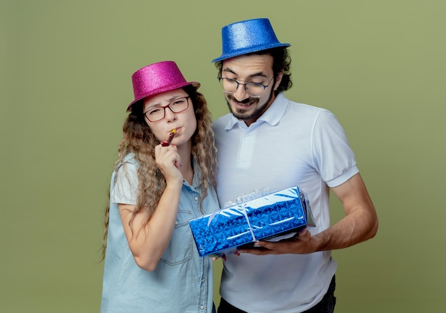 Giovane coppia che indossa rosa e blu cappello ragazza che soffia fischio e ragazzo che tiene e guardando la confezione regalo isolata sulla parete verde oliva