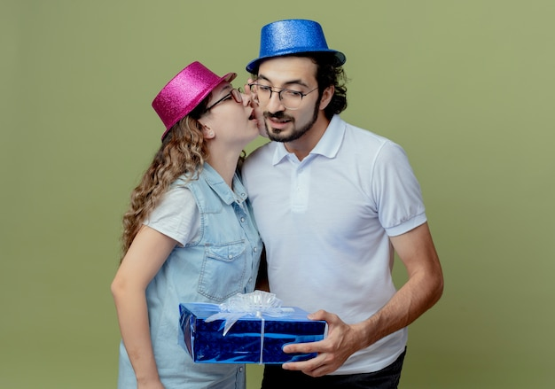 Giovani coppie che portano il sussurro rosa e blu della ragazza del cappello sull'orecchio del ragazzo e sul contenitore di regalo della tenuta del ragazzo isolato su verde oliva