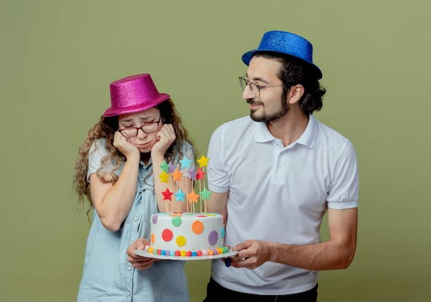 Young couple wearing pink and blue hat pleased guy gives birthday cake to sad girl isolated on olive green