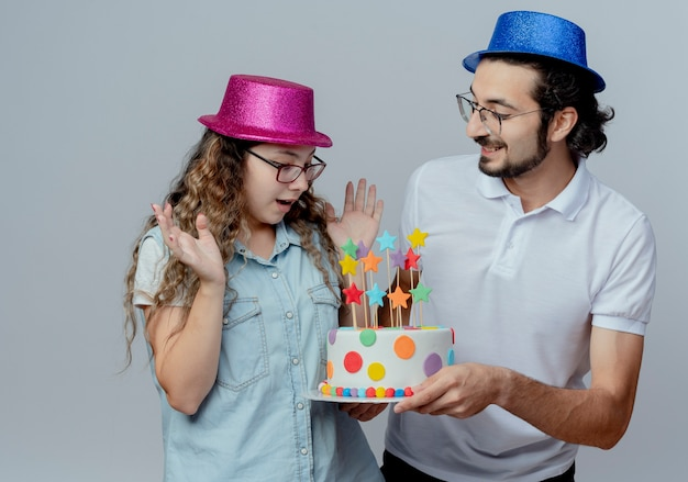 Young couple wearing pink and blue hat pleased guy gives birthday cake to surprised girl isolated on white