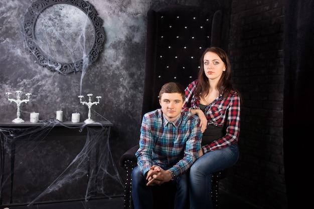 으스스한 유령의 집 설정에서 높은 등받이 의자에 함께 앉아 격자 무늬 셔츠를 입고 젊은 부부
