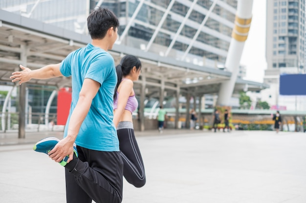 Young couple wearing sportswear with stretching exercise in the city