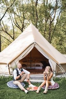 Young couple wearing stylish boho casual clothes sitting on the pillows on green grass in front of big wigwam tent outdoors