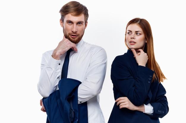 Молодая пара в костюмах стоит рядом с коллегами по работе, общающимися по финансам