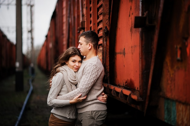 Young couple wearing on tied warm sweaters hugging in love at railway stations