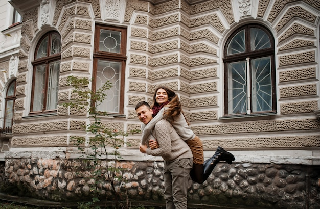 Young couple wearing on tied warm sweaters in love. girl girl on neck of her boyfriend. lovers background old building on city.