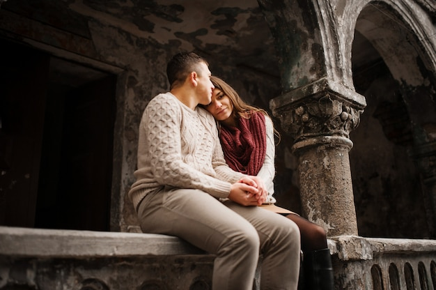 Young couple wearing on tied warm sweaters in love sitting on stone baluster at old yard with arch and columns at city.