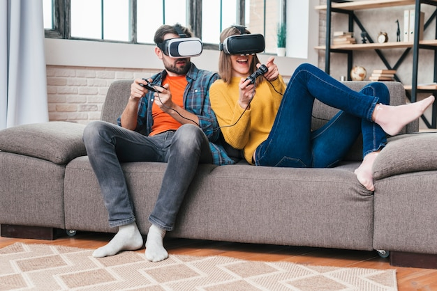 Young couple wearing virtual reality glasses playing the video game