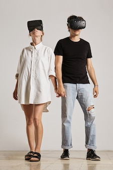 A young couple wearing vr headsets holding hands looking in different directions in a room with white walls and wooden floors