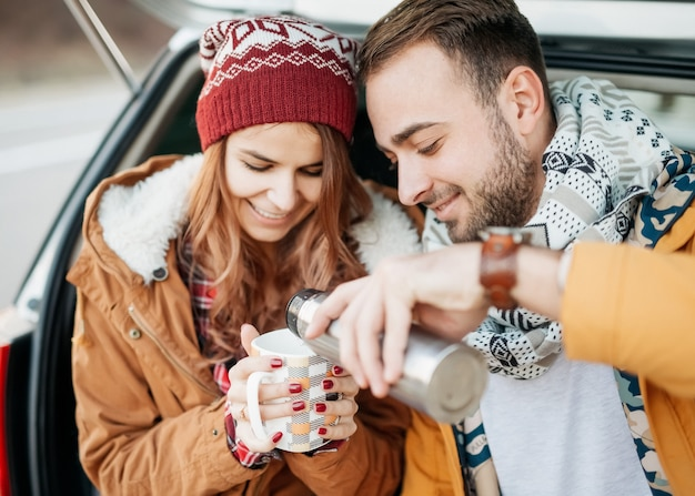 暖かい服を着て、冬の日に熱いお茶を飲む若いカップル。