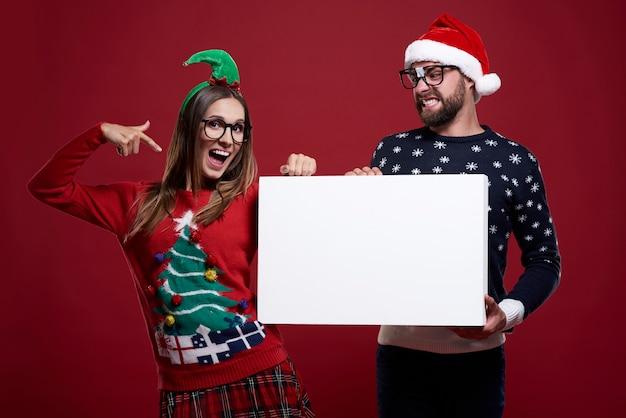 Giovani coppie in vestiti strani di natale che tengono documento in bianco