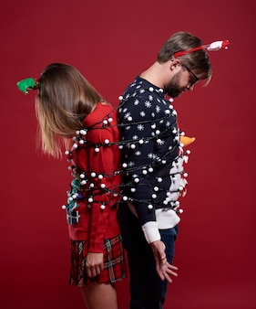 Giovane coppia in strani vestiti di natale legati con luci di natale