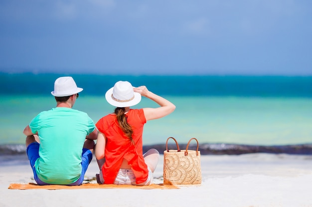 Young couple on white beach. woman in red shirt and beach bag