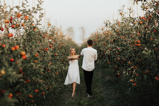 Young couple in white clothes circling in the midst of apples garden. the woman holding on to the strong hands of her man.