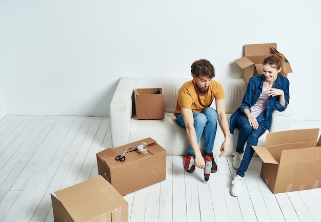 Young couple on white couch with boxes of fun chatting.
