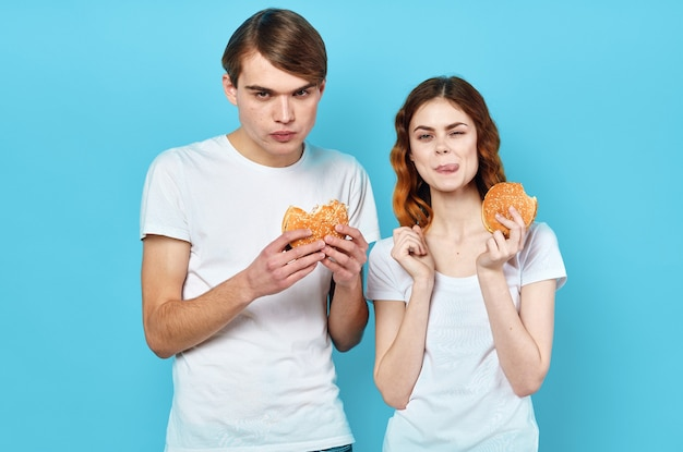 Young couple in white t-shirts with hamburgers in their hands fast food snack. high quality photo