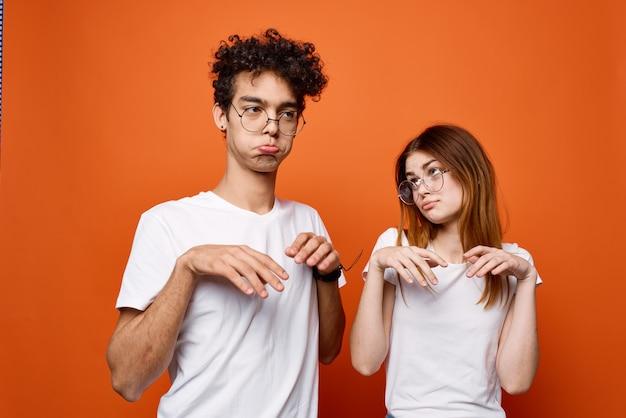 若いカップルの白いtシャツ楽しいファッションオレンジ色の背景