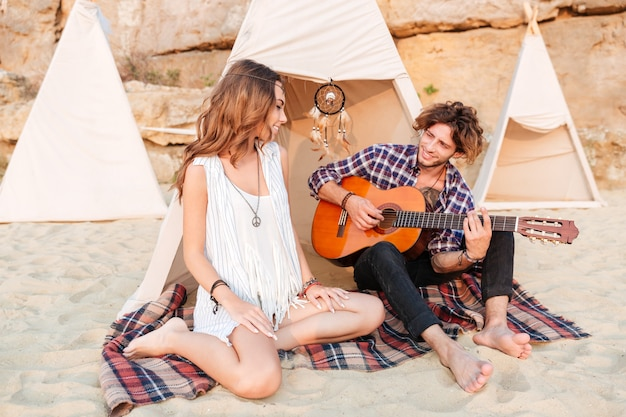 Young couple in wigwam on the beach