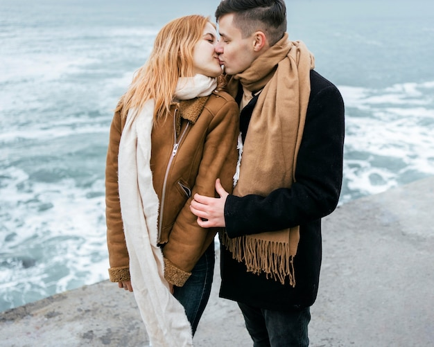Young couple in winter kissing by the beach