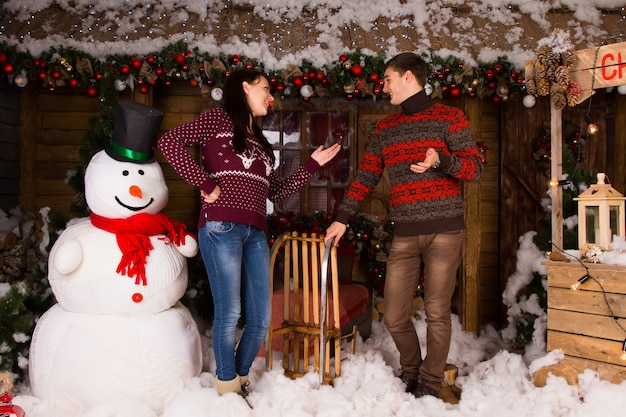 Young couple in winter outfits talking inside the wooden house, with various attractive christmas decors, beside big indoor snowman.