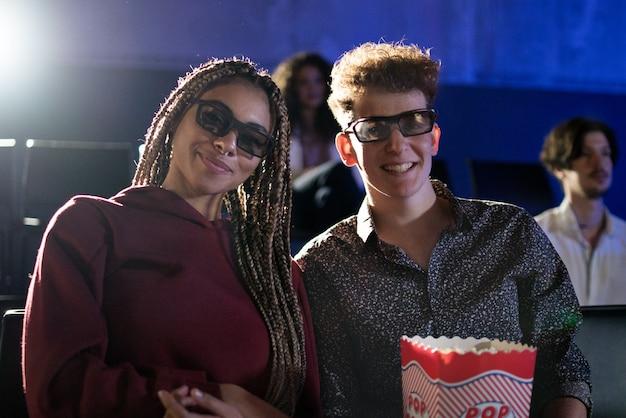 映画館で映画を見ながら、カメラを見ながら、3dメガネとポップコーンを持つ若いカップル。