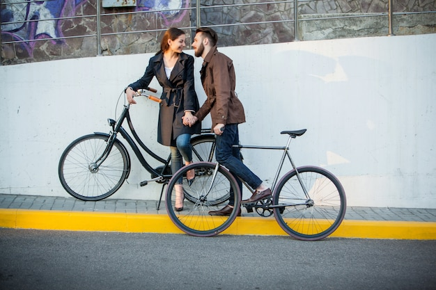 Молодая пара с велосипедом напротив города