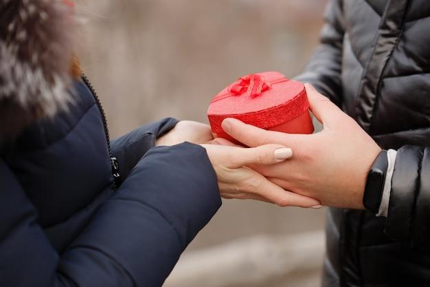 그들의 손에 선물을 가진 젊은 부부 세인트 발렌타인 데이에 대한 개념