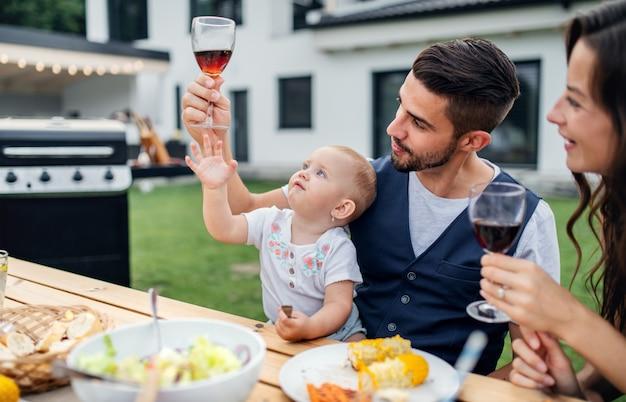 家族の庭のバーベキューで屋外のテーブルに座って、ワインを飲む赤ちゃんと若いカップル。