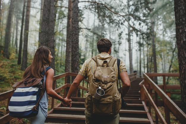 Young couple with backpacks hiking in the forest